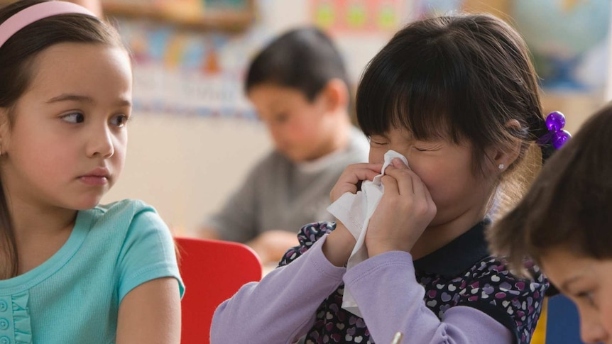 A girl is blowing her nose while sitting in between two classmates