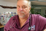 close up of man leaning on a clinic reception counter wearing a purple work shirt and a stethoscope