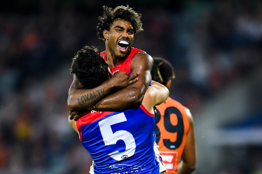 An overjoyed AFL forward is lifted up by a teammate after kicking a goal.