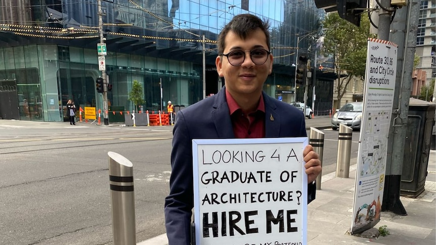 A young man dressed in a suit stands with a sing that reads looking 4 a graduate of architecture HIRE ME?