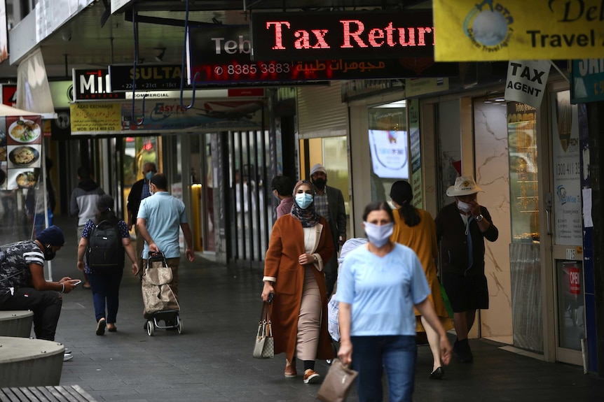 People wearing masks walk along the path in a strip mall in Auburn. There are a number of shop signs