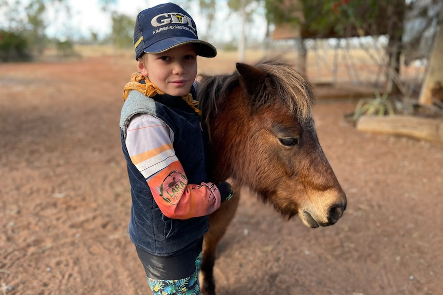 Jodie Muntelwit's son holding the neck of a small horse