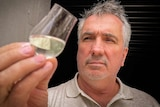 William McHenry examining a glass of his alcoholic product.