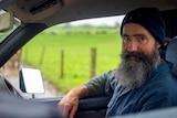 A dairy farmer sitting in a car on his farm wearing a blue beanie