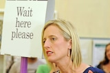 ACT Labor leader Katy Gallagher stands next to a 'Wait here please' sign to cast her ballot on October 20, 2012.