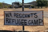A sign strung up on the side of the street says 'WA residents refugee camp'