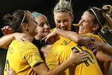 Five Matildas players embrace in celebration of a goal.