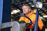 Jason Hawkins operates a forklift.