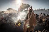Smoke rises at the start of a ceremony led by an Indigenous man as a crowd stands watching.