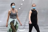 Two women in face masks cross deserted road.