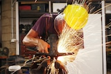 Armourer Joel Hunter wearing protecting equipment while he works with a propane torch.