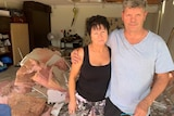 Man and woman stand with arms around each other in damaged home