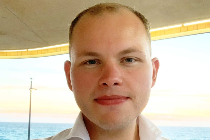 A close up of a man with very short hair on a boat