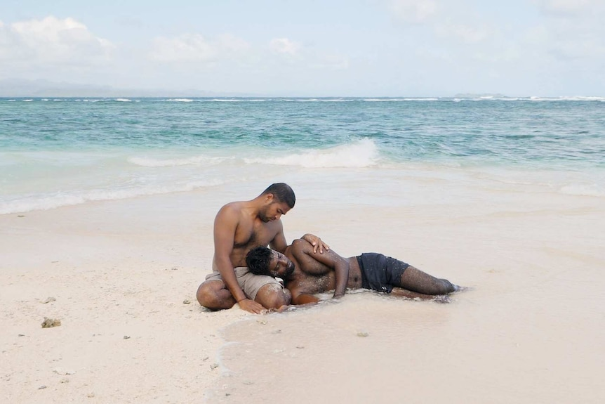 A still from Hoda Afshar's video work Remain, two refugees lie in the sand of a beach on Manus Island