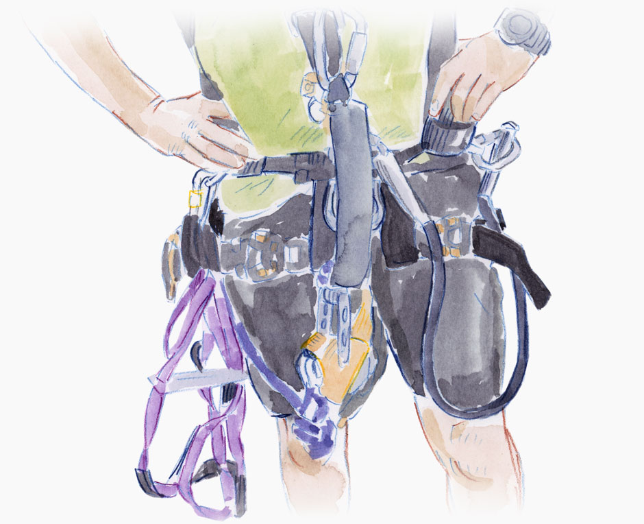 Torso of a man and the abseiling equipment he wears.