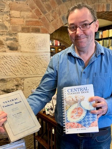A man in a blue shirt and glasses holds two editions of a cook book.