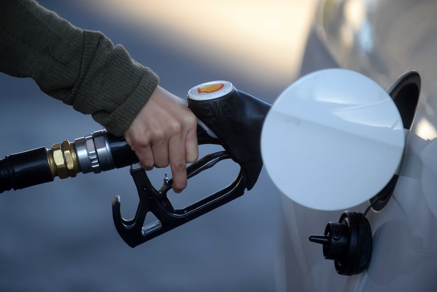 A hand holding a fuel nozzle putting petrol in a white car