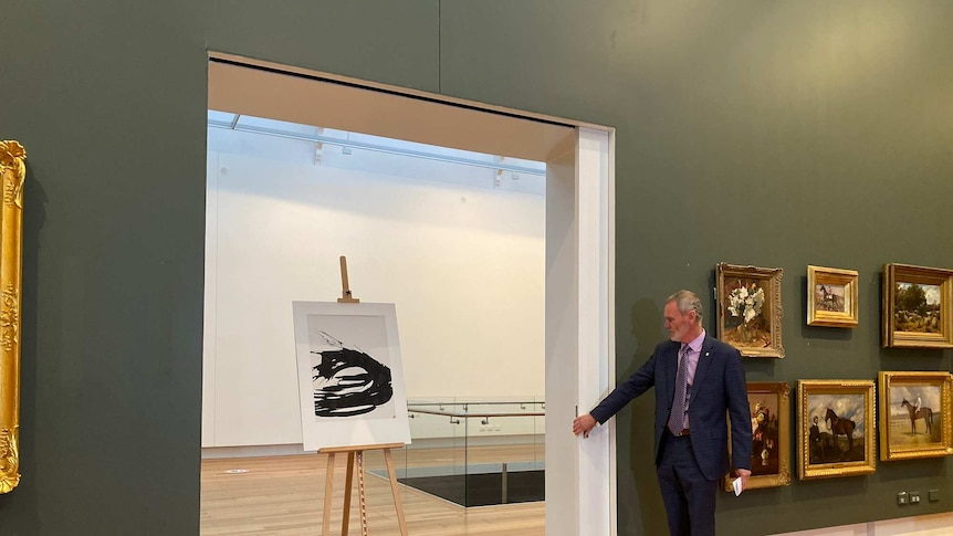 A black and white ink drawing stands on an easel in an art gallery.