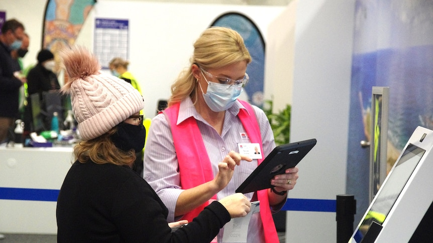 Staff from Hunter New England Health assist people as they arrive at Belmont mass vaccination hub