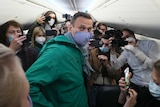 Alexei Navalny is surrounded by journalists inside the plane prior to his flight to Moscow.
