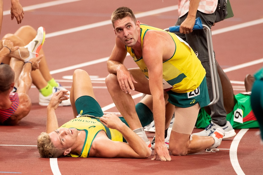 Ash Moloney lies on the ground with Cedric Dubler kneeling on the track over him after the decathlon.