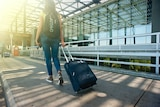A woman holding a suitcase on wheels walks away from the camera.