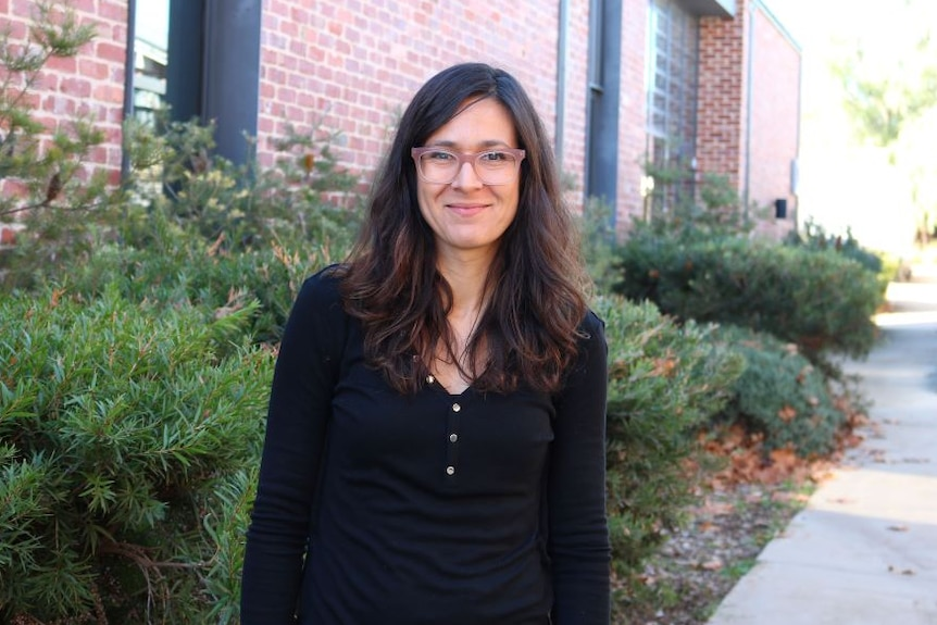 A woman with long brown hair and glasses stands in front of a red brick building wearing a black shirt.