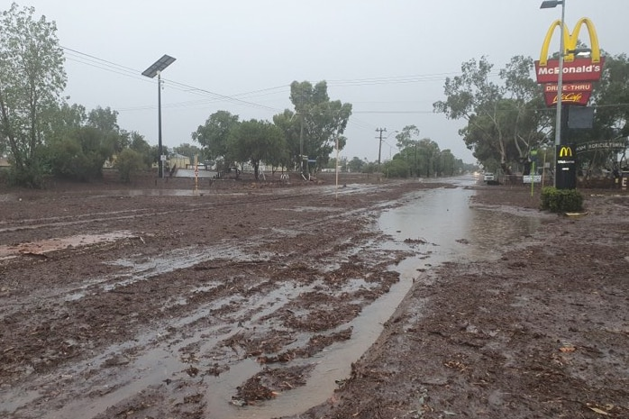 A road is covered in brown mud and water with fast food signage.