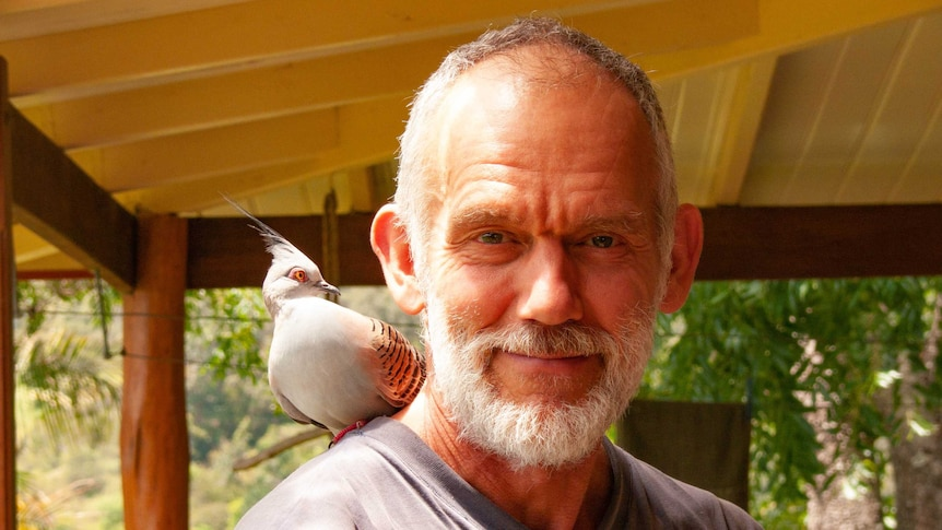 A balding man with a grey beard with a dove sitting on his shoulder, smiles at the camera.