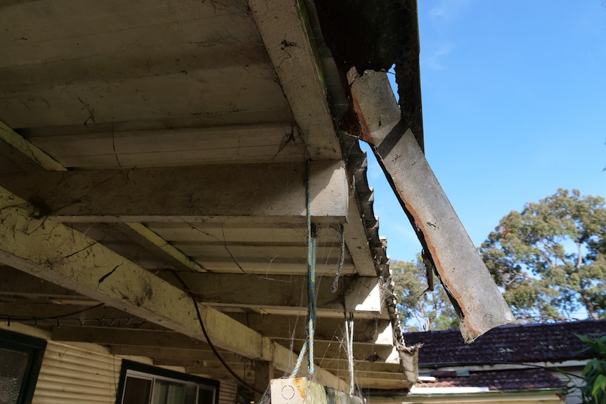 A jagged piece of rusty guttering hangs down at an angle off the veranda roofing.