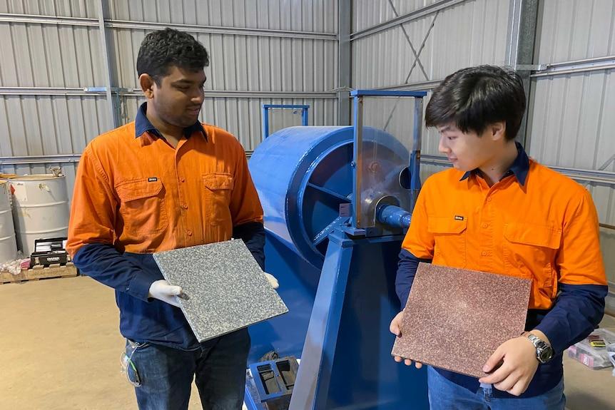 Two men in hi-vis orange shirts hold a tile each in a shed