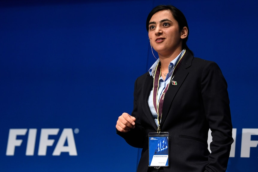 An Afghan woman speaks on stage at an international football inclusion conference in Switzerland.