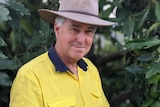 Man stands in front of tree in hi vis with hat