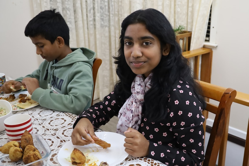 A young boy and girl sitting at their kitchen table observing Ramadan.