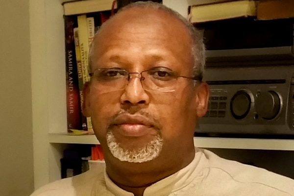 Dr Hussein Haraco, wearing a cream shirt and glasses, sits in front of a bookshelf.