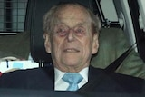Prince Philip stares ahead as he sits in the car. His seatbelt is secured, and there is a man in a tweed jacket behind.