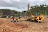 Drilling machinery on dirt near ar mining pit.