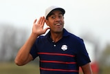 Tony Finau cups his hand to his ear and smiles
