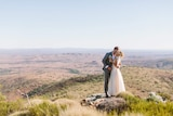 A photo of a bride and groom on a clifftop at a rural property