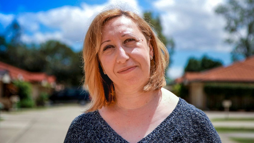 A profile shot of a woman with short blonde-brown hair standing in front of an out-of-focus suburban background.