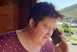 Woman with short red hair, wearing a red shirt with white polka dots talking on a mobile phone outside of a house
