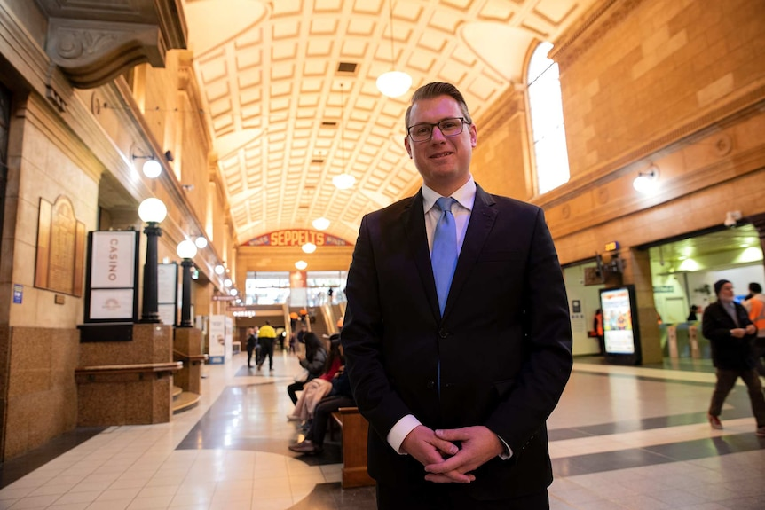 A bespectacled middle-aged man wearing a dark suit and a powder-blue tie stands in a transport interchange of some kind.