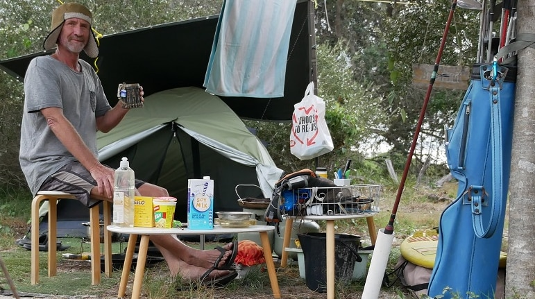 A man holds a mug of tea as he sits on a stool under a suspended tarpaulin in front of a tent set up in the bush.