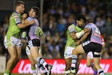 Iosia Soliola of the Raiders is tackled by Wade Graham