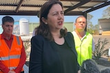 Annastacia Palaszczuk stands under a shed talking to the media with men wearing high viz vests on either side of her