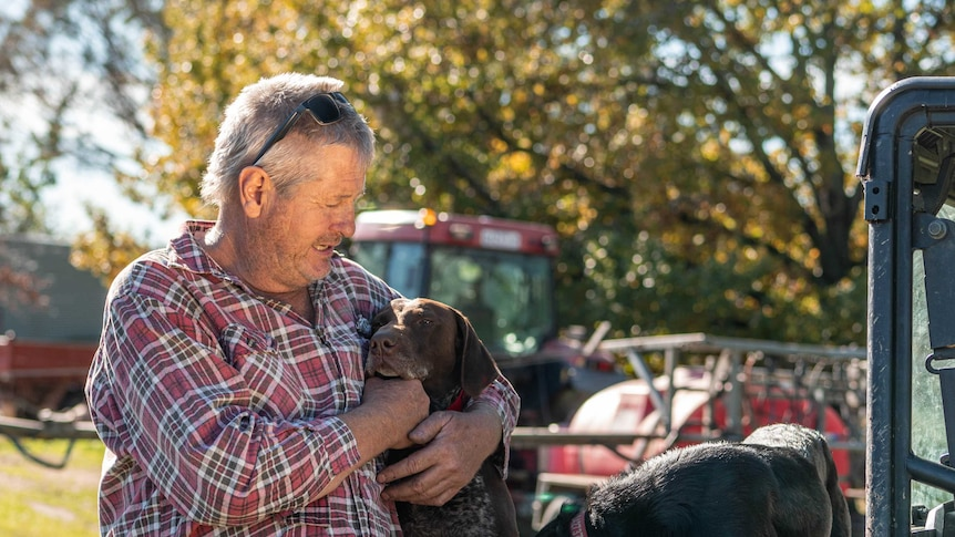 A man with grey hair, wearing a flannelette shirt, hugs his dog which is sitting on the back of a farm vehicle.