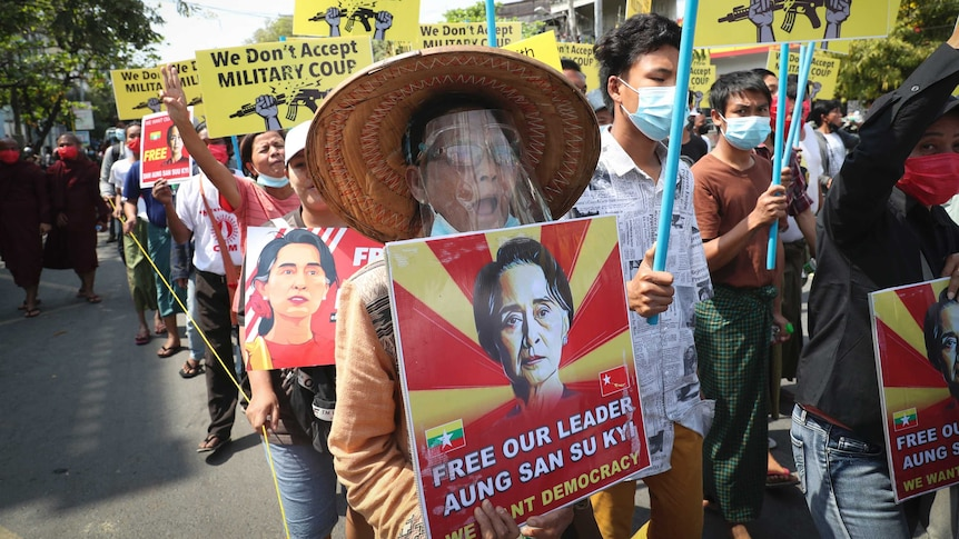 "A large crowd of protesters carrying signs reading ""we don't accept military coup"" and ""free out leader Aung San Suu Kyi""."