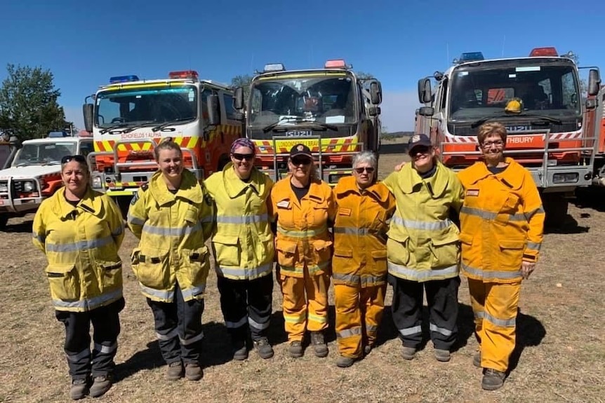 Seven women in various shades of yellow bushfire protective gear stand arm-in-arm in front of three large fire fighting tankers