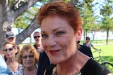 A tight head shot of a smiling Pauline Hanson with people standing behind her.