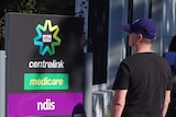 People line up outdoors beside a Centrelink sign.